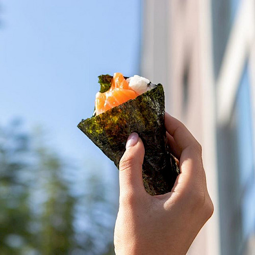 Person holding salmon sushi hand-roll